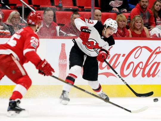 New Jersey Devils center Nico Hischier (13), of Switzerland, passes the puck against Detroit Red Wings defenseman Mike Green (25) during the first period of an NHL hockey game Saturday, Nov. 25, 2017, in Detroit.