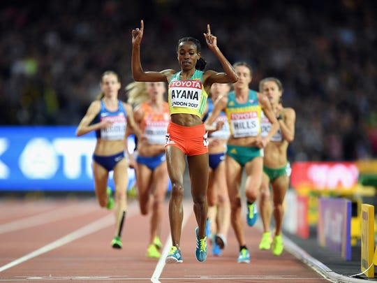 Almaz Ayana of Ethiopia celebrates her victory in the women's 10,000 meters Saturday at Olympic Stadium in London. Molly Huddle is at the far left on her penultimate lap.