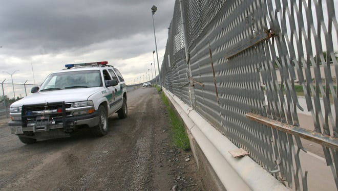 A Border Patrol vehicle drives past a portion of the border fence, in El Paso, Texas.