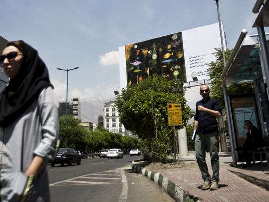 Iranians wait at a bus station next to a billboard