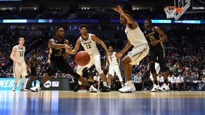 Florida State Seminoles guard Trent Forrest (3) passes against Xavier Musketeers forward Kaiser Gates (22) during the second half in the second round of the 2018 NCAA Tournament at Bridgestone Arena.