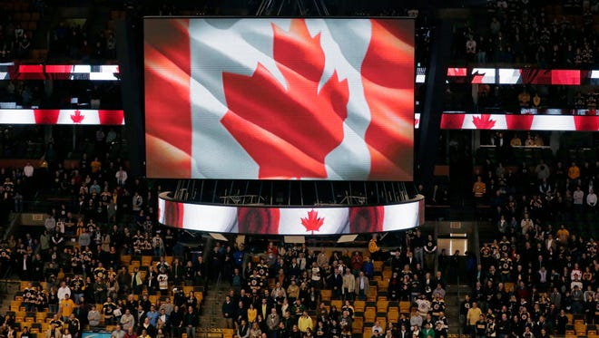 Fans stand for the Canadian national anthem prior to an NHL hockey game between the Boston Bruins and New York Islanders in Boston, Thursday Oct. 23, 2014.