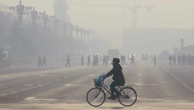 "This file photo taken on Dec. 21, 2015 shows a woman wearing a mask as she rides her bicycle along a street near Tiananmen Square on the third day of a ""red alert"" for pollution in Beijing on December 21, 2015."