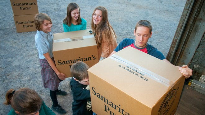 Members of the University Presbyterian Church Youth Group help load up boxes of donated goods for children onto a truck bound for Denver at the First Evangelical Free Church on Wednesday as part of Operation Christmas Child. Last year the project collected more than 6,000 shoe boxes filled with school supplies, candy and other items for distribution to 120 countries as well as several American Indian reservations.