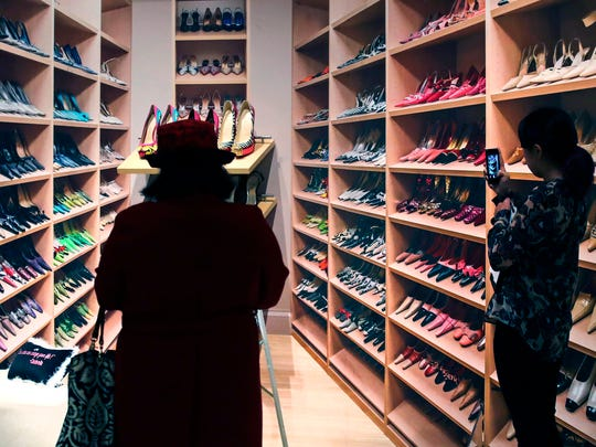 "In this Tuesday, Nov. 15, 2016 photo, guests snap images of a shoe closet display at the Peabody Essex Museum in Salem, Mass. From flats to stilettos, what we put on our feet says something about who we are. That's the premise of new exhibition in Massachusetts. ""Shoes: Pleasure and Pain"" opens Saturday, Nov. 19, 2016, at the Peabody Essex Museum in Salem."