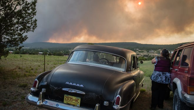"""Residents of the town, Chilili, along state road 337 watch as the Dog Head Fire inches closer to their town, southeast of Albuquerque, N.M., Wednesday June 15, 2016. Authorities don't have a containment estimate yet for a wildfire burning in the Manzano Mountains southeast of Albuquerque but say good weather helped firefighters attack the fire overnight. The so-called """"Dog Head Fire"""" in part of the Cibola National Forest east of Los Lunas started Tuesday and grew to over a square mile by Wednesday morning after its growth slowed overnight."""