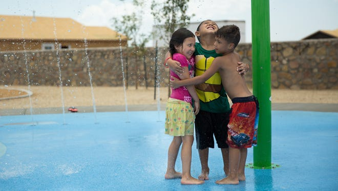 Leighyah Calles, 4, from left, Eddie Chavez III, 6, and Micah Eggleston, 6, group hug waiting for a bucket of water to fall on them, July 18, 2016, as they play at Metro Verde Park Splash Pad, July 18, 2016. Vandals tagged certain portions of the newly opened Metro Verde Park over the weekend.