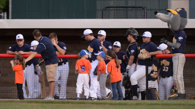 Young baseball players stand with the RiverRats before a baseball game at McBride Stadium Thursday, July 3, 2014.
