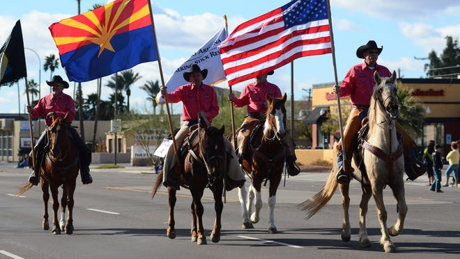 Flag-bearing cowboys on horseback pass by during the start of the the 60th annual Parada del Sol Parade in Scottsdale.