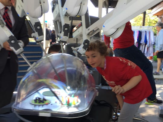 Erin O'Donnell, 9 of New Paltz, takes a look at the da Vinci Xi surgical robot during Saturday's Prostate Cancer Walk at Walkway Over the Hudson State Park.