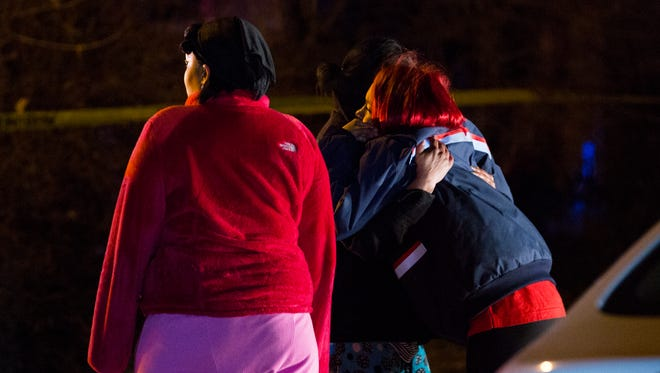 Family members of the victim embrace at the crime scene tape.
