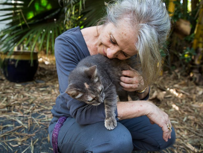 Heather Burch nestles with Julia, one of the many cats