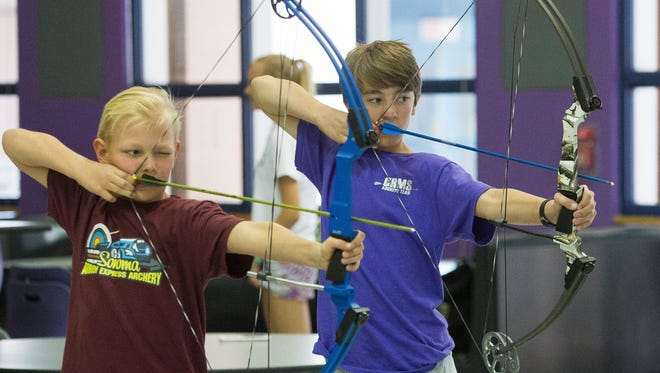 Jacob Estep,13, right, and Jaeton Monroe, 10, left, demonstrate their archery skills in the Camino Real Middle School Cafeteria, Thursday April 19, 2018.