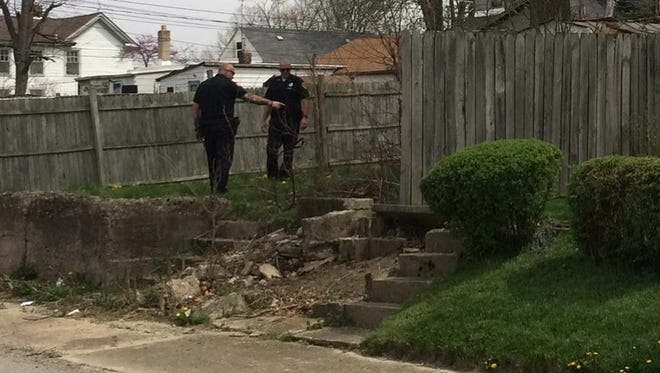 Richmond Police Department Officer Danny Barron and Officer Ron Pennington search a yard while trying to locate a handgun Tuesday.