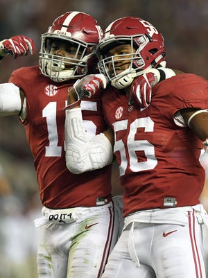 Alabama defensive back Ronnie Harrison (15) and linebacker Tim Williams (56) celebrate their tackles for loss on Saturday against Auburn.