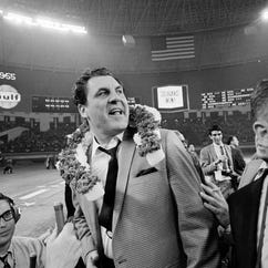 Guy V. Lewis, University of Houston basketball coach, wears a garland of flowers after the Houston Cougars upset the UCLA Bruins in the Houston Astrodome,
