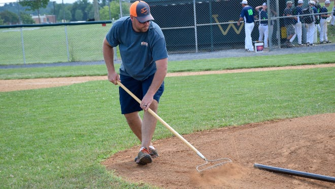 Volunteer Brian Welcher rakes the pitcher's mound between games at the 13-year-old Babe Ruth League state tournament on Thursday, July 15, 2016, at Wilson Memorial High School's Bo Bowers Stadium in Fishersville.
