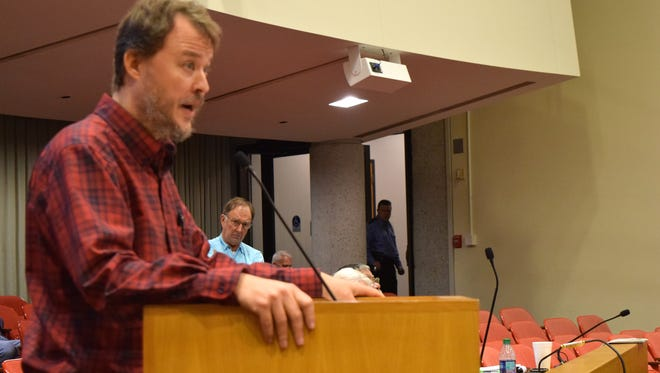 """River Sports owner Ed McAlister stands behind Kevin Hill of Uncle Lem's Outfitters on Jan. 23 as Hill asks the Knox County Commission to investigate the possibility of an """"unfair"""" bidding process. River Sports won the bid over Uncle Lem's."""