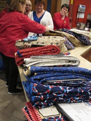 Members of Quilts of Valor unpack quilts for 15 homeless