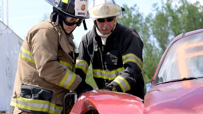 """State Senator Curtis Hertel, D-Lansing, uses the the """"jaws of life"""" to help cut the frame of a car Monday, May 18, 2015, during Fire Operations 101 training at Lansing Community College."""