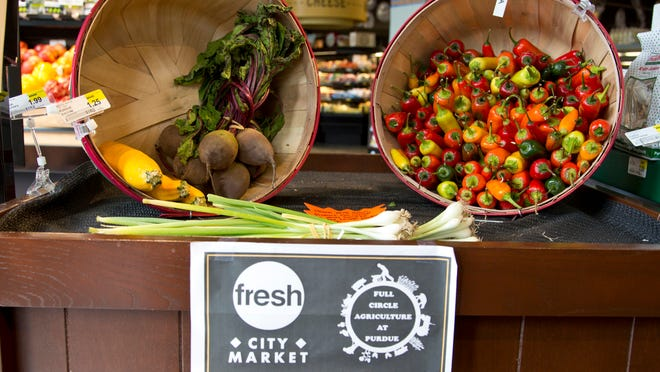 The Purdue Student Farm table displays local produce at Fresh City Market in West Lafayette.