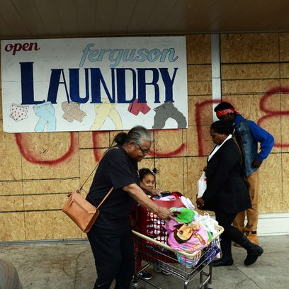 People walk past a laundry with covered windows and