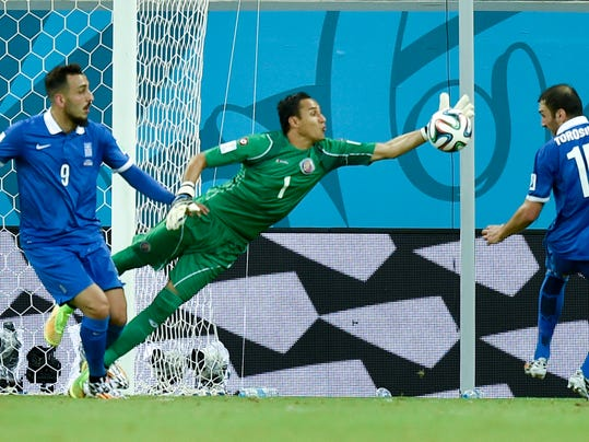 Costa Rica's goalkeeper Keylor Navas clears the ball away from Greece's Kostas Mitroglou (9) and Vasilis Torosidis during the World Cup round of 16 soccer match between Costa Rica and Greece at the Arena Pernambuco in Recife, Brazil, Sunday, June 29, 2014. (AP Photo/Martin Meissner)