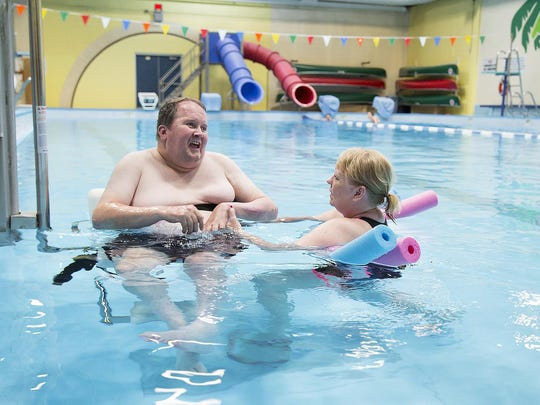 Chris Northcutt, left, and Marybeth Holskey, dip in the pool at the Morony Natatorium at the beginning of a swim therapy session.