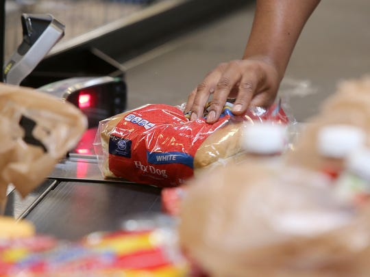 Cashier Kimberly Smith rings up a package of hot dog buns while checking out Annette Spain at the Kroger on University Parkway.