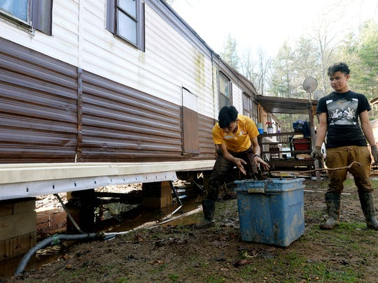 Jorge Caballero, let, and his brother, Lester, 16, clean up debris around their trailer home after Gashes Creek behind the home on Fernwood Drive flooded in rains Monday night on Tuesday, Dec. 29, 2015. Families on the street had been cleaning debris since about 6 a.m.