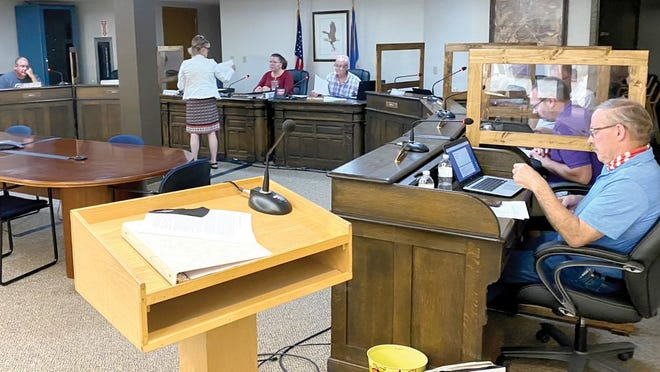 "At this week's Crookston City Council Ways & Means Committee, Laurie Stahlecker of the Crookston Visitors Bureau distributes documents to council members, Interim City Administrator Angel Weasner and Mayor Dale Stainbrook. It was the council's first meeting since dividers were placed between council members. Asked by the Times about the lack of masks being worn by council members and city officials, Weasner said ""Executive Order 20-81 Section 10 c states that masks may be temporarily removed for governmental meetings subject to the open meeting law to ensure everyone may be heard clearly."""