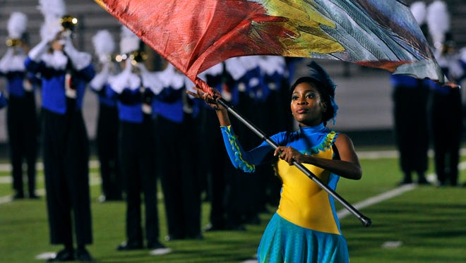 Cooper High School senior Kedecia Tomlinson performs with the Awesome Cooper Band color guard during the Big Country Marching Festival on Oct. 16 at Wylie High School's Bulldog Stadium, site of Monday's UIL region contest.