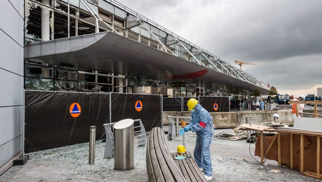 In this March 23, 2016 file photo, a forensics officer works in front of the damaged Zaventem Airport terminal in Brussels.