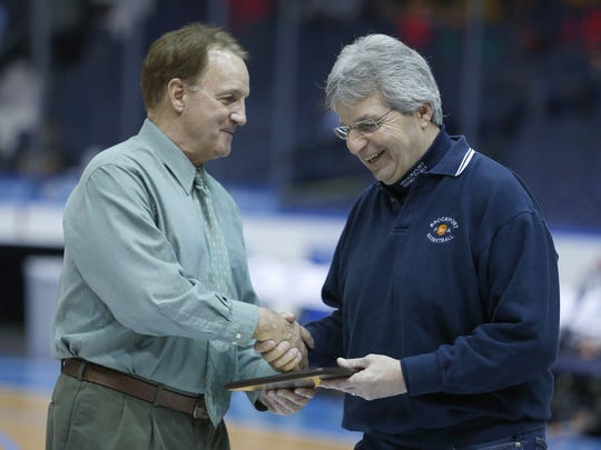 Jack Purificato, left, who is retiring as Section V boys basketball chairman, hands an award to Charlie Hage, former Brockport High School boys basketball coach this past Saturday at the Blue Cross Arena at the War Memorial.