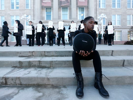 Ravyn Brooks holds a speakers playing an alleged audio