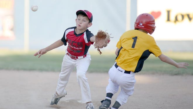 Boonville Ready Mix shortstop Race Leonard reaches for the ball while Bradley Automotive's Ben Oeth tries to avoid the tag in the fourth inning Thursday night in Cal Ripken Minor. Boonville Ready Mix improved to 2-0 by beating Bradley Automotive 11-6.