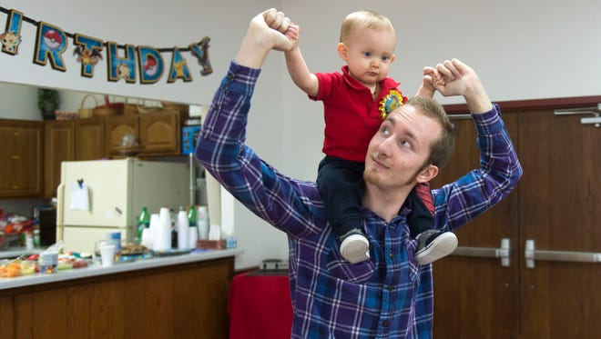 Kurtis McCarter gives his son Asher a piggy-back ride during his first birthday celebration March 11, 2017, at French Broad Valley Baptist Church.
