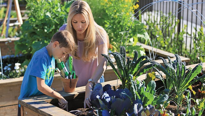 Rancho Mission Viejo employee Stephanie Walker teaches resident Braden Taylor how to plant seeds at one of the agrihood's farms.