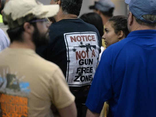 A fan wearing a pro-gun T-shirt waits in line for an