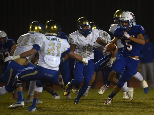Reno's Ty Silver (5) runs while taking on Reed during