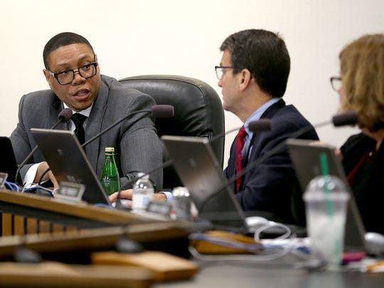 IPS superintendent Lewis Ferebee talks to board member Michael Connor, right, at the IPS meeting where board voted to close three high schools Monday, Sept. 18, 2017.
