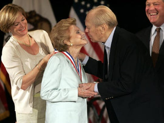 Susan Ford Bales presents the Gerald R. Ford medal to her mother Betty Ford as former President Gerald R. Ford prepares to kiss her next to his son Mike Ford, during the Gerald R. Ford Foundation Dinner at The Lodge in Rancho Mirage.