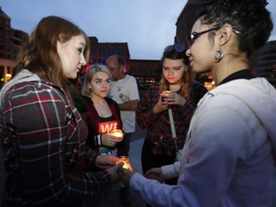 Kelsey Burgess, 22, left, Amanda Konieczny, 19, Samantha Konieczny 18, and Aki Madsen, 18, all of Wausau, gather in a circle during a candlelight vigil event Sunday at 400 Block in downtown Wausau. This candlelight vigil for the Sunday mass shooting in Orlando, Florida.