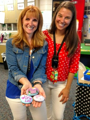 Parkview Elementary third-grade teachers Bridget Zahradnik, left, and Alexandra Sanchez. Zahradnik holds rocks painted by students for the new outdoor classroom at the school, which will be worked on this summer.