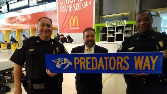 Metro police Capt. David Corman and Cmdr. John Drake stand with Nashville Predators CEO Sean Henry on June 5, 2017. They were holding a street sign renaming Fifth Avenue South to Predators Way through the end of June.