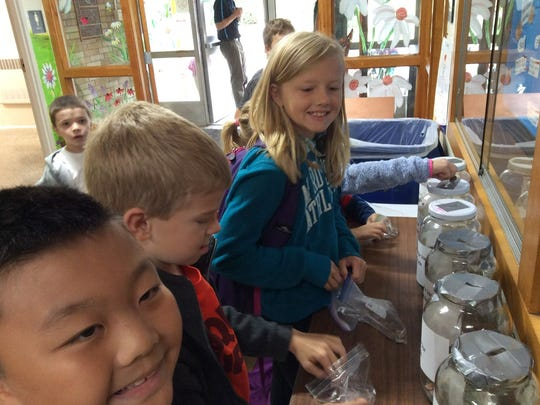 Hatley Elementary School students sort out their penny war donations.