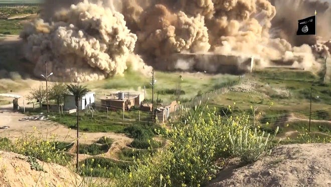 An image taken from a video made available by Jihadist media outlet Welayat Nineveh on April 11 allegedly shows smoke billowing from an ancient site after it was wired with explosives by Islamic State  in northern Iraq.
