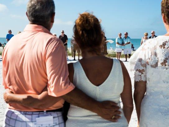Steve and Linda Vinelli, back center right, hold hands