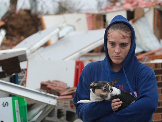 "Shaylyn Jeffery holds the building owner's dog ""Payday"""