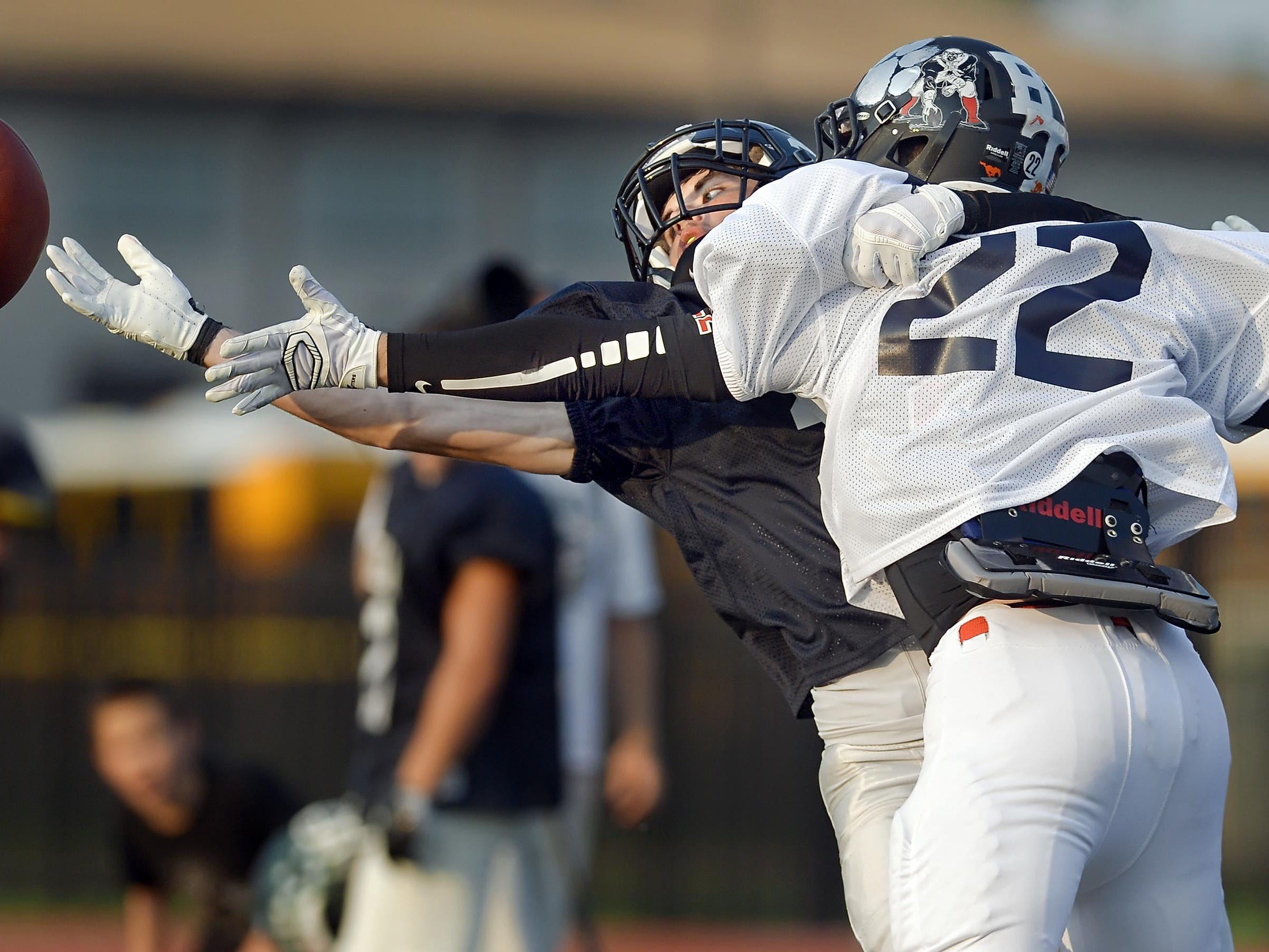 LeRoy's Ryan McQuillen, left, reaches for a tipped pass while defended by Penfield's Brian McCandless during the 33rd Annual Eddie Meath All-Star Game played at Eastridge High School on Saturday, July 11, 2015.